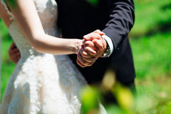 Closeup of newlyweds hands reach out while they dance. In the garden royalty free stock photo