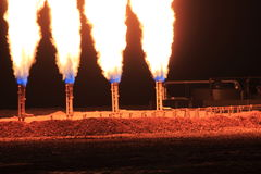 Closeup Night Shot of Quad Gas Flare. Four gas flares after a frack job in the Bakken. Waste gas is flared as a byproduct of oil production due to poor economic Royalty Free Stock Photography