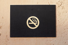 Closeup of no smoking sign warning board on wall Stock Photo