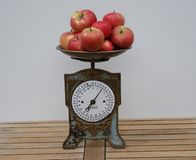 Closeup of a nostalgic kitchen scale with apples on the scales pan stock photo