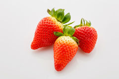 Closeup of not fully ripe strawberries. Over white background Stock Photos