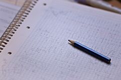 Closeup of a notebook full of mathematical operations next to pencil