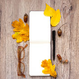Closeup of notebook, glasses and pen, decorated with autumn yellow leaves and branches. Top view, flat lay Royalty Free Stock Photos