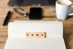 Closeup on notebook over wood table background, focus on wooden blocks with letters making News word Stock Photo