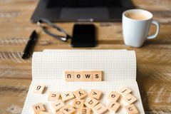 Closeup on notebook over wood table background, focus on wooden blocks with letters making News word Stock Photos