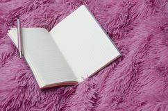 Closeup of notebook,pen on pink modern fluffy plaid.Blank sheets.Women style stock images