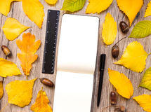 Closeup of notebook, ruler and pen, decorated with autumn yellow leaves and acorns. Top view, flat lay Royalty Free Stock Images