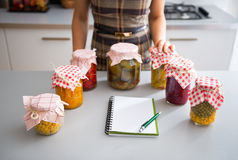 Closeup on notepad and housewife with jars royalty free stock images