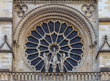 Closeup of the Notre Dame de Paris Cathedral facade with the oldest rose window installed in 1225 which forms a halo above the royalty free stock images