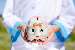 Closeup of nurse's hands holding piggy bank in. Picture of nurse's hands holding piggy bank. Closeup of ceramic moneybox on blurred outdoor background Royalty Free Stock Images