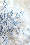 Closeup o snowflake and stars. Closeup of snowflake with shimmering lights in background Royalty Free Stock Photo