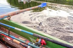 Oar paddle from row boat. Closeup of oar paddle from row boat moving in water on green lake with ripples. Camping tourism relax trip active lifestyle adventure stock photos