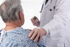 Free Closeup Of A Elderly Male Patient Wearing A Hospital Gown As A Doctor Places His Hand On His Shoulder Offering Comfort Royalty Free Stock Photos - 171382978