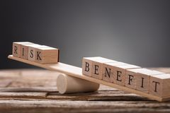 Free Closeup Of Risk And Benefit Wooden Blocks On Seesaw Stock Images - 124523294