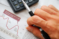 Closeup Of Writing Hand And Financial Documents Royalty Free Stock Photos