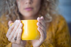 Free Closeup Of Yellow Cup Of Tea Or Coffee -caucasian Woman Holding Hot Beverage At Home Indoor - Quarantine Covid-19 Coronavirus Royalty Free Stock Images - 177747519