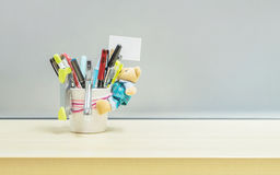 Closeup office equipment and color pen in desk tidy cup for pen on blurred wooden desk and frosted glass wall textured background Royalty Free Stock Photo