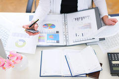 Closeup on office table and working business woman Stock Photos