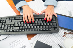 Closeup office womans fingers with red nailpolish writing on computer keyboard using both hands Stock Images