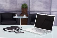 Closeup office workplace. Closeup photo of laptop, personal organizer and mobilephone placed on desktop in office Royalty Free Stock Image