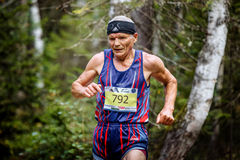 Closeup of old active male athlete running in woods. Zlatoust, Russia - August 28, 2016: closeup of old active male athlete running in woods during Mountain Royalty Free Stock Image