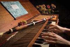Playing on an old baroque clavichord and wooden traverse flute. Closeup of an old baroque clavichord and wooden traverse flute hands playing Stock Photos