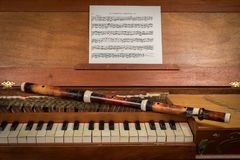 An old baroque clavichord and wooden traverse flute. Closeup of an old baroque clavichord and wooden traverse flute Royalty Free Stock Photography