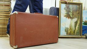 Old case on foreground and modern bags behind picture. Closeup old brown case on foreground and loader hides modern colorful cases behind beautiful picture stock video