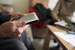 Old man using a tablet and old woman reading. Closeup of an old caucasian man using a tablet and an old caucasian man reading a magazine, sitting both in a couch Royalty Free Stock Image