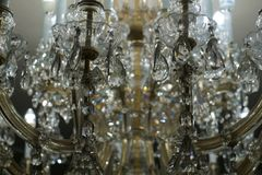 Prisms and Crystals on Glass Chandelier. Closeup of this old crystal chandelier shows the etched glass and prisms capturing the light royalty free stock image