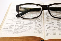 Closeup of old dictionary and glasses. Closeup of old dictionary and black glasses royalty free stock photos