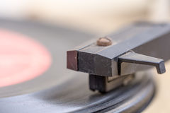 Closeup of old and dusty vinyl record player with arm and needle in focus Royalty Free Stock Photos