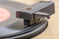 Closeup of old and dusty vinyl record player with arm and needle in focus Royalty Free Stock Images