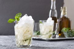 Closeup of old-fashioned glass of mint julep against tray with alcohol beverage, gasses and mint, grey colors royalty free stock photo