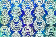 Vintage printed damask repeat pattern. A closeup of an old fashioned shabby blue and white damask flower pattern printed on a paper background stock photo