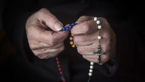 Closeup of old female hands praying with rosary stock photo