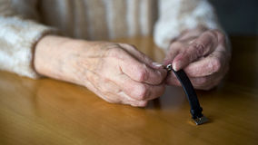 Closeup of old female hands setting the time wristwatch royalty free stock photography