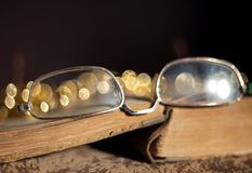 Old glasses lying on a vintage book with a blurred background and beautiful bokeh royalty free stock photo