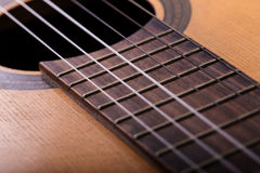 Closeup of old guitar body with sound hole and strings Royalty Free Stock Photos
