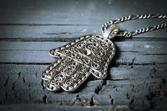Old hamsa amulet or hand of fatima. Closeup of an old hamsa amulet, also known of the hand of fatima or the hand of mary, on a gray rustic wooden surface royalty free stock images