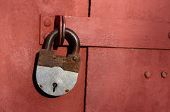 Closeup of old lock on red metal garage door Stock Images