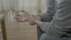 Closeup of old man with arthritis touching his painful wrist having rheumatism sitting on the couch at home - stock footage