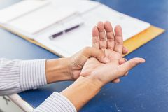 Closeup old man hand palm joint tendon muscle pain. After writing work hard in office stock photos
