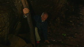 Closeup Old Man Holds Trunk Tries to Get out Dark Cave stock video footage