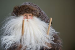 Closeup of old man winter with ski poles. Realistic, antique fur-trimmed mountain trapper holds ski poles at the ready Royalty Free Stock Images