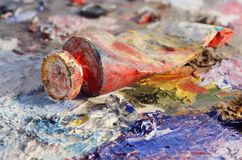 Closeup of old oil paint tube with red colour lying on palette Stock Images