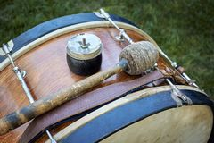Closeup of an old orchestral big drum. Closeup of an old orchestral big drum with a shock stick on the grass in the city park Royalty Free Stock Images