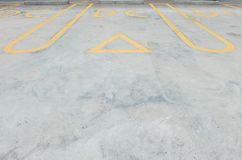 Closeup surface old and pale yellow painted sign for parking slot line on cement street floor in the car park with DC word sign te. Closeup old and pale yellow Royalty Free Stock Photo