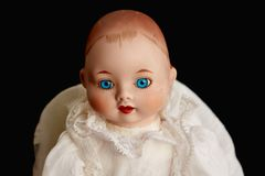 Closeup of old porcelain doll with blue eyes on black background Royalty Free Stock Photos
