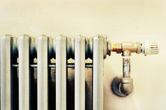 Closeup of an old radiator with a new thermostat Stock Photography